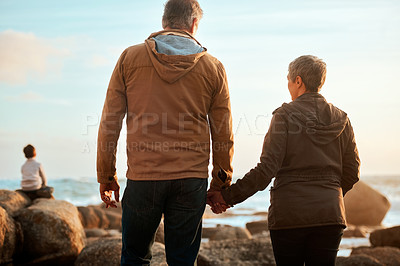 Buy stock photo Rearview of a senior couple standing hand in hand while watching their grandson at the beach