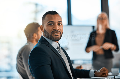 Buy stock photo Portrait of a young businessman sitting in an office with his colleagues in the background