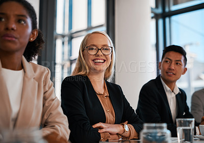 Buy stock photo Portrait of a young businesswoman sitting alongside her colleagues during a meeting in an office