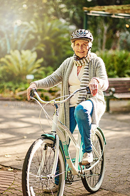 Buy stock photo Shot of a senior woman going for a bicycle ride in the park