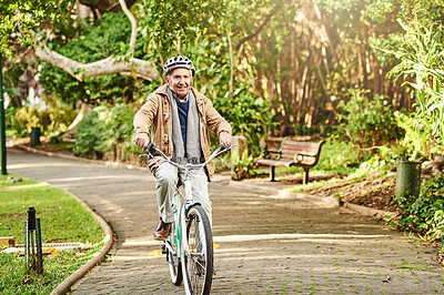 Buy stock photo Shot of a senior man riding his bicycle through a park