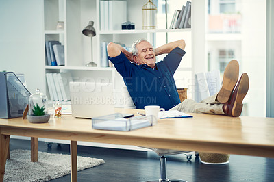 Buy stock photo Shot of a senior businessman sitting with his hands behind his head and feet up on the table while working from home