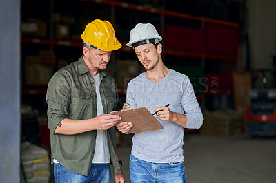 Buy stock photo Cropped shot of two male construction workers looking over some paperwork while standing in an industrial warehouse