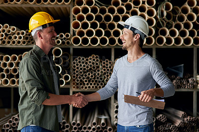 Buy stock photo Cropped shot of two male construction workers shaking hands while standing in an industrial warehouse