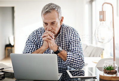 Buy stock photo Shot of a mature man looking anxious while working on a laptop at home