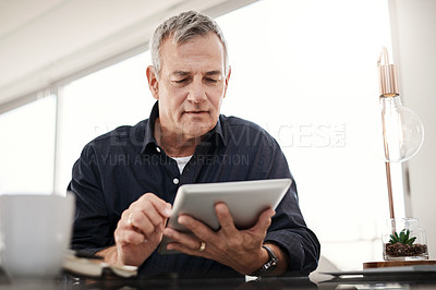 Buy stock photo Shot of a mature man working on a digital tablet at home