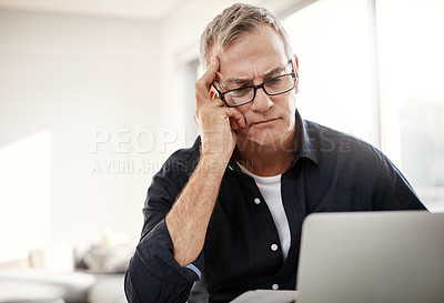 Buy stock photo Shot of a mature man looking stressed out while working on a laptop at home