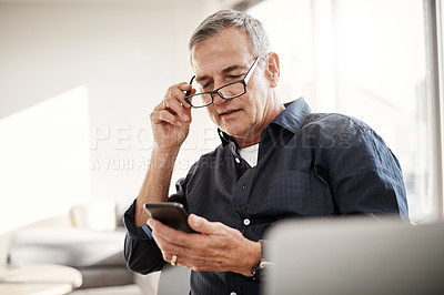 Buy stock photo Shot of a mature man using a cellphone at home