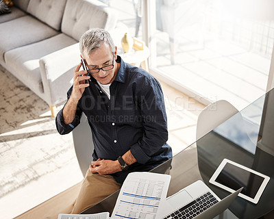 Buy stock photo High angle shot of a mature man talking on a cellphone at home