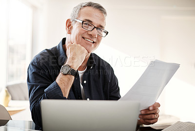 Buy stock photo Portrait of a mature man going through some paperwork at home