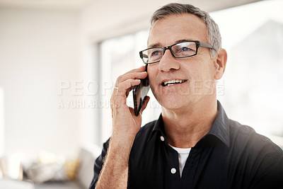 Buy stock photo Shot of a mature man talking on a cellphone at home