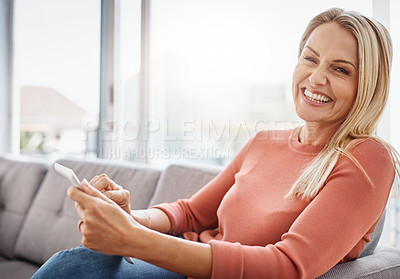 Buy stock photo Portrait of an attractive mature woman using a digital tablet while relaxing on the sofa at home