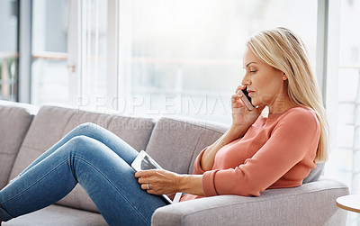 Buy stock photo Shot of an attractive mature woman using a mobile phone and digital tablet while relaxing on the sofa at home