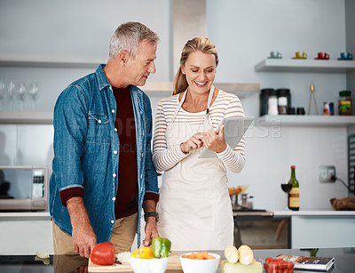 Buy stock photo Shot of a couple looking at a digital tablet while cooking in the kitchen