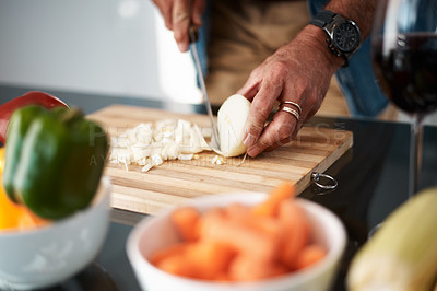 Buy stock photo Cropped shot of an unrecognizable man chopping onions on a cutting board