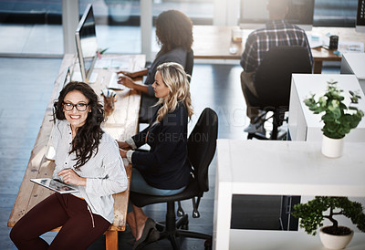 Buy stock photo Portrait of a businesswoman using a digital tablet in an office with her colleagues working in the background