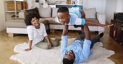 Buy stock photo Shot of a young family spending time together in the living room at home