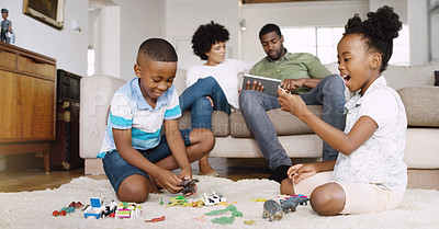 Buy stock photo Shot of an adorable little brother and sister playing with toys together on the floor while their parents are using a tablet while chilling on the sofa at home