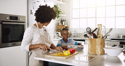 Buy stock photo Cropped shot of young beautiful mother making food with her son's help in the kitchen at home