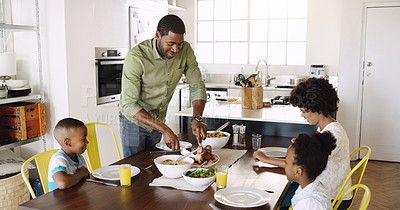Buy stock photo Cropped shot of a father dishing food for his family while they having lunch at the dining table at home