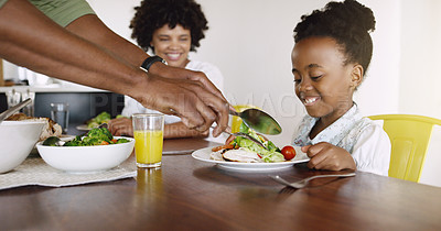 Buy stock photo Cropped shot of an unrecognizable father dishing food for his adorable little daughter at home