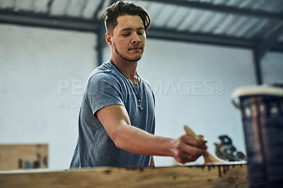 Buy stock photo Cropped shot of a carpenter varnishing wood in his workshop