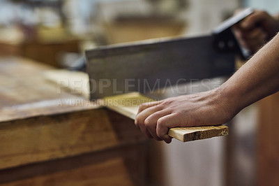 Buy stock photo Cropped shot of a carpenter cutting material in his workshop