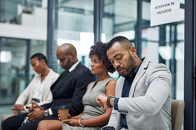 Buy stock photo Cropped shot of a handsome young businessman checking the time while waiting in line for his interview