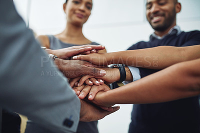 Buy stock photo Low angle shot of a group of businesspeople standing in the office with their hands in a huddle