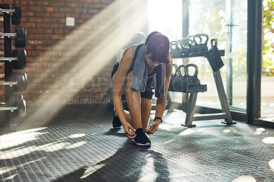 Buy stock photo Shot of a young woman tying her shoelaces in a gym