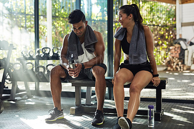 Buy stock photo Shot of a young couple taking a break together in a gym
