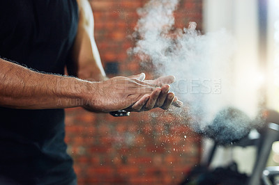 Buy stock photo Cropped shot of a man dusting his hands with powder in a gym