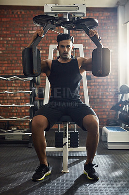 Buy stock photo Shot of a young man working out with an exercise machine in a gym