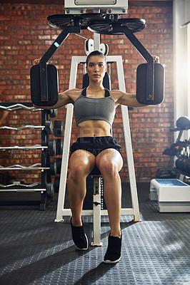 Buy stock photo Shot of a young woman working out with an exercise machine in a gym