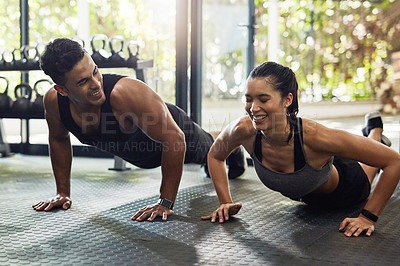 Buy stock photo Shot of a young couple doing pushups together in a gym
