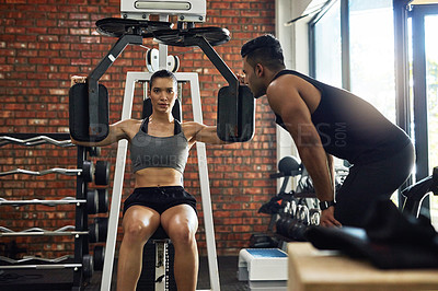Buy stock photo Shot of a young woman working out with an exercise machine with her boyfriend looking on
