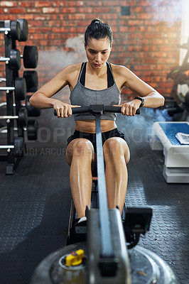 Buy stock photo Shot of a young woman using a rowing machine in a gym