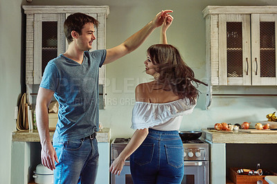 Buy stock photo Shot of a young couple dancing together at home