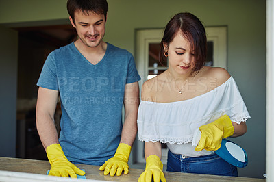 Buy stock photo Shot of a young couple cleaning a surface at home