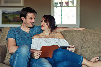 Buy stock photo Shot of a young couple reading a magazine together at home