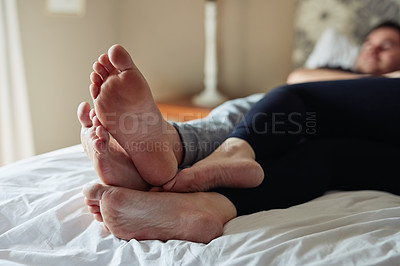 Buy stock photo Shot of an affectionate couple's feet relaxing together on the bed at home