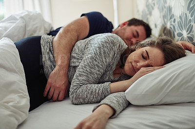 Buy stock photo Shot of a young couple sleeping peacefully together in bed