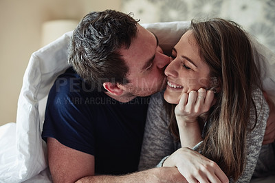 Buy stock photo Shot of a happy young couple covering themselves with a blanket and kissing on the bed at home