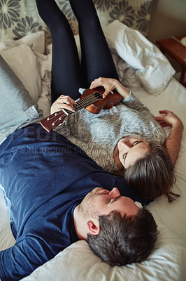 Buy stock photo High angle shot of a young couple playing the ukulele while relaxing on the bed at home
