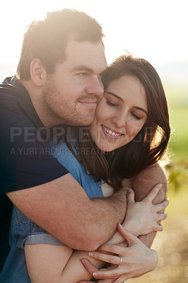 Buy stock photo Shot of a happy young couple hugging in the park