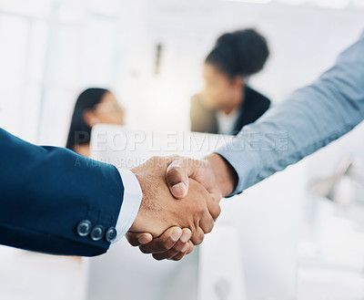 Buy stock photo Cropped shot of two businesspeople shaking hands in an office