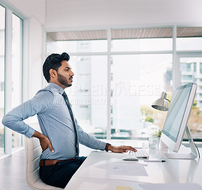 Buy stock photo Cropped shot of a young businessman suffering from back pain while sitting at his desk