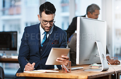 Buy stock photo Cropped shot of a handsome young businessman working at his desk in a modern office
