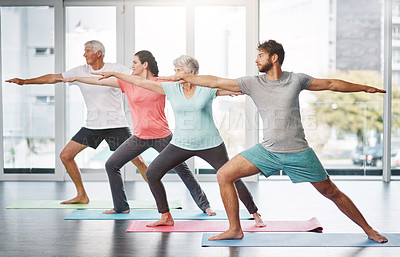 Buy stock photo Full length shot of a group of people practicing yoga