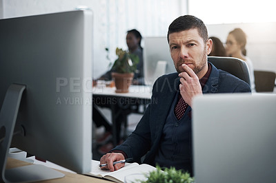 Buy stock photo Shot of a mature businessman using a computer at his desk in a modern office